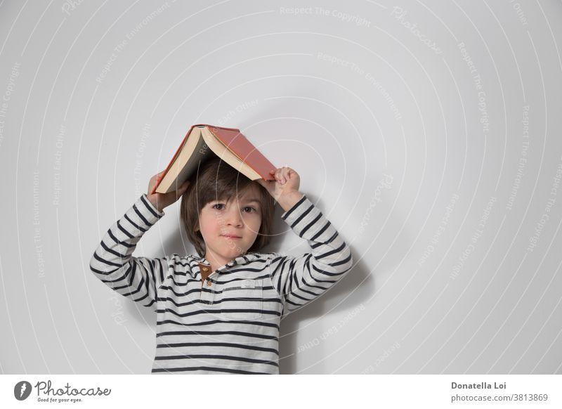Kinderporträt mit Buch auf dem Kopf bezaubernd Junge Kaukasier heiter Kindheit niedlich Tag Bildung Emotion Ausdruck Gesicht Spaß Fröhlichkeit Glück Beteiligung