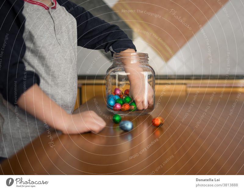 Kind nimmt Pralinen aus der Dose zu Hause Feier Kindheit Schokolade farbig Konzept Verlangen Ostern Eier Glasgefäß Gier gierig gierige Nahrung Hand Hände Küche