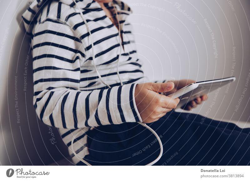 Kind mit Tablette auf dem Boden sitzend Sucht Kaukasier Kindheit Mitteilung Computer Konzept verbinden Anschluss Gerät digital digitales Tablett Anzeige Bildung