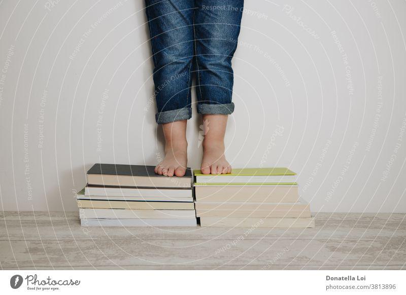 Kind steht auf einem Bücherstapel Barfuß Freizeitkleidung Kaukasier Kindheit Konzept Bildung lehrreich Fuß Spaß wachsen heimwärts Hausaufgabe im Innenbereich