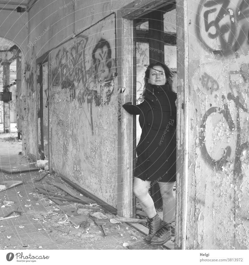 für bitti - langhaarige Frau im schwarzen Mantel steht in einer Türöffnung eines alten maroden Gebäudes Mensch Lost Place Wand Türrahmen Graffiti kaputt