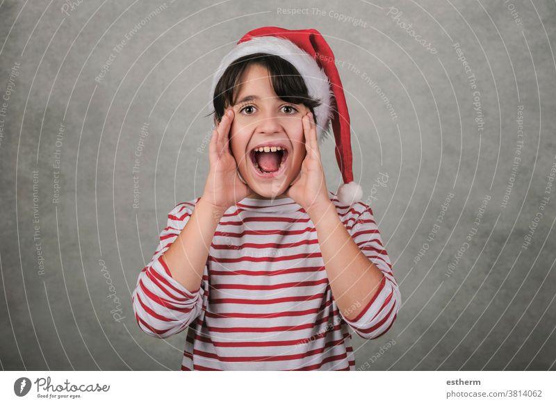 Frohe Weihnachten, schreiendes Kind mit Weihnachtsmannmütze Schrei schreit Heiligabend verrückt aufgeregt Ankündigung ankündigen positiv gestikulieren gestresst