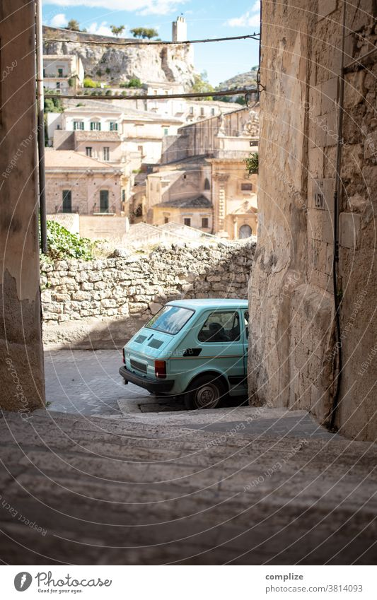 Kleines Auto in einer Gasse auf Sizilien auto oldtimer sizilien modica gasse eng altstadt historisch vintage patina straße urban treppe haus häuser