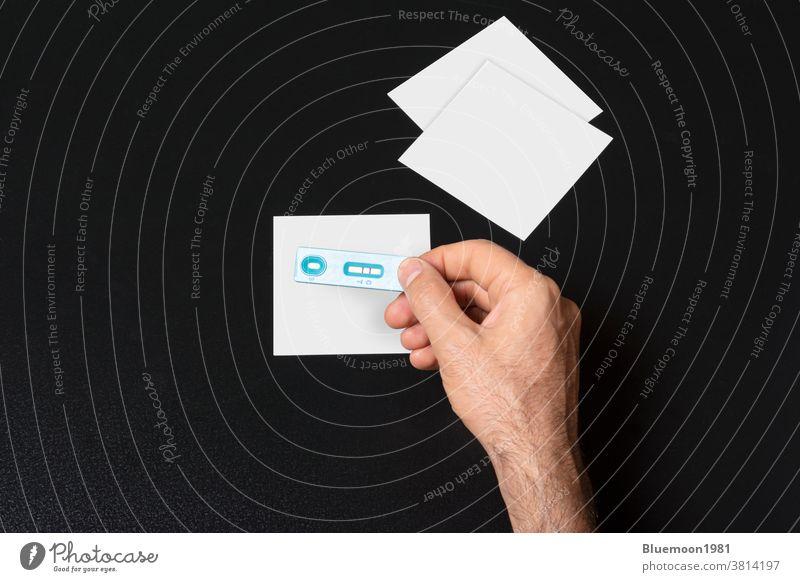 Eine Hand, die einen Schwangerschaftstest vor dem Mock-up eines Bilderrahmens hält Attrappe editierbar Wandel & Veränderung Prüfung positiv Halt klein Papier