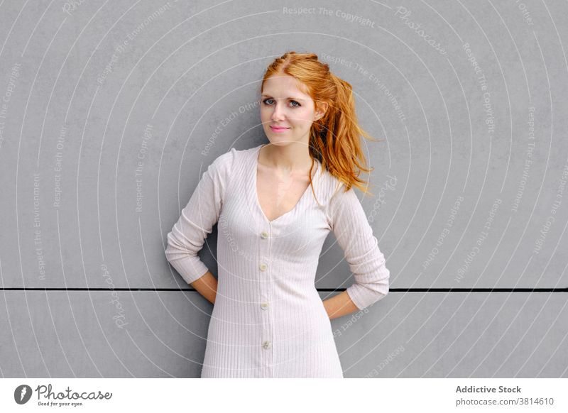 Junge rothaarige Frau steht in der Nähe von grauen Wand rote Haare urban Kleid Stil positiv trendy jung Rotschopf Lächeln selbstbewusst Zeitgenosse Mode Inhalt