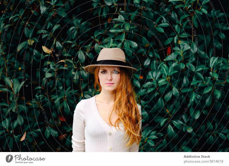 Junge Frau mit Hut im Garten stehend Stil Rotschopf trendy rote Haare modern Ingwer Mode jung lange Haare Dame selbstbewusst charmant Lifestyle elegant
