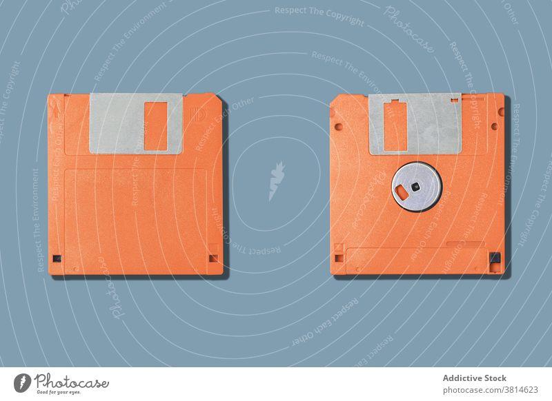 Computer-Disketten auf grauem Hintergrund Floppy zwei Lamelle alt pc altmodisch Information Daten veraltet orange Gerät Werkzeug altehrwürdig retro Accessoire