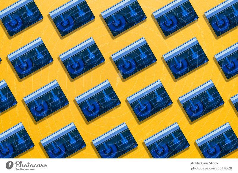 Blaue Vintage-Kassetten auf gelbem Hintergrund Klebeband Audio retro blau Kulisse altehrwürdig altmodisch kompakt durchsichtig analog Musik stereo veraltet