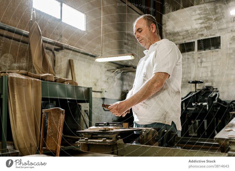 Männlicher Meister bei der Arbeit in der Schreinerei Werkstatt Tischlerin Holzarbeiten Mann Zimmerer ernst Kleinunternehmen Hobelbank männlich hölzern Garage