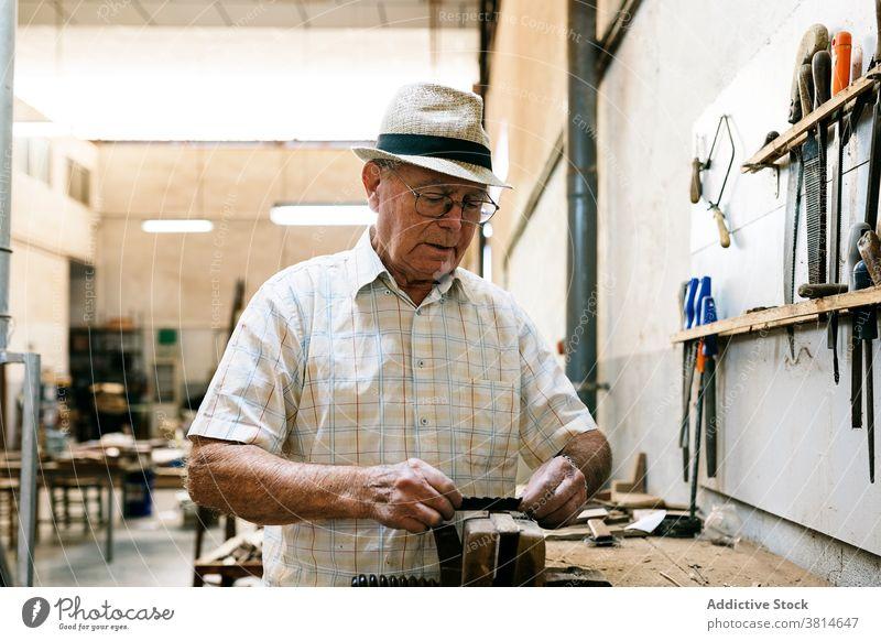 Älterer männlicher Holzarbeiter bei der Arbeit in der Garage Grinden Schreinerei Werkstatt Mann Zimmerer Tischlerin Holzarbeiten Pferch Ventilator handgefertigt