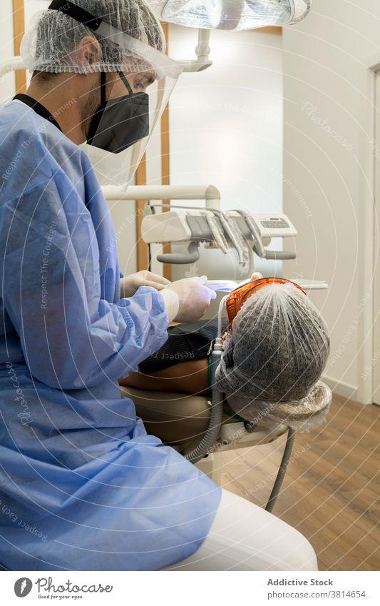 Zahnarzt behandelt Zähne eines Patienten mit UV-Licht ultraviolett Gerät Zahnmedizin Kur Stomatologie Werkzeug dental professionell Klinik Medizin mündlich