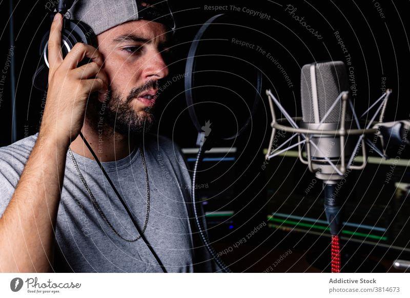 Mann im Aufnahmestudio Aufzeichnen Atelier Mikrofon singen Künstler Hut Sänger Kopfhörer akustisch schäumen männlich Klang Beweis Gesang Raum Musik Musiker