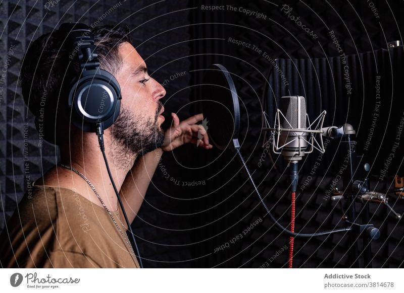 Mann im Aufnahmestudio Aufzeichnen Atelier Mikrofon singen Künstler Sänger Kopfhörer akustisch schäumen männlich Klang Beweis Gesang Raum Musik Musiker modern