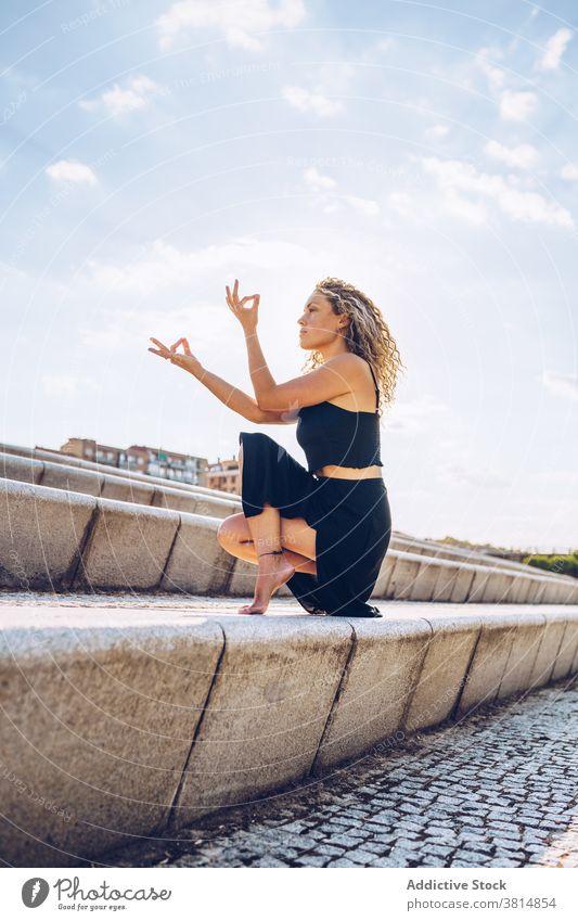 Fokussierte Frau übt Yoga-Meditation auf Stufen meditieren Zehenstand Mudra Asana Padangusthasana Gleichgewicht Zen beweglich Pose üben positionieren Wellness