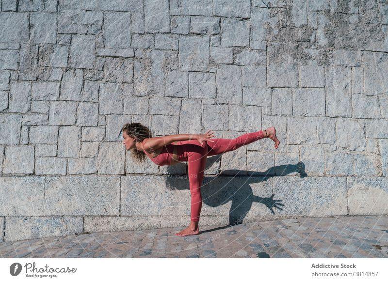 Schlanke Frau stehend in Warrior-Yoga-Pose Krieger Variation Gleichgewicht Asana beweglich üben positionieren schlank Wellness Harmonie Wohlbefinden Aktivität