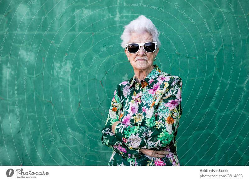 Stilvolle ältere Frau mit trendiger Sonnenbrille Senior trendy Hipster cool farbenfroh Outfit Mode urban Lifestyle hell Individualität verrückt Glück heiter