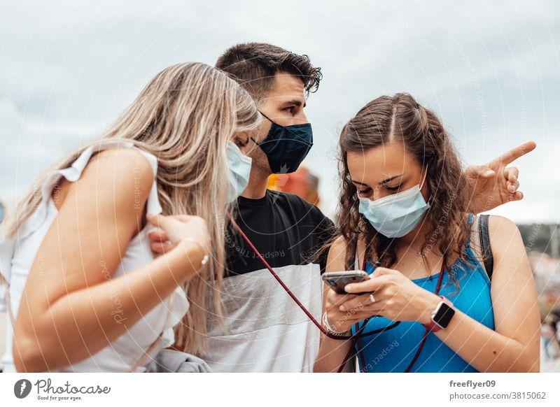 Gruppe von Freunden mit chirurgischen Masken, die auf einem Smartphone suchen Orientierung Menschengruppe Kaukasier zwanglose Kleidung durchsuchend Telefon