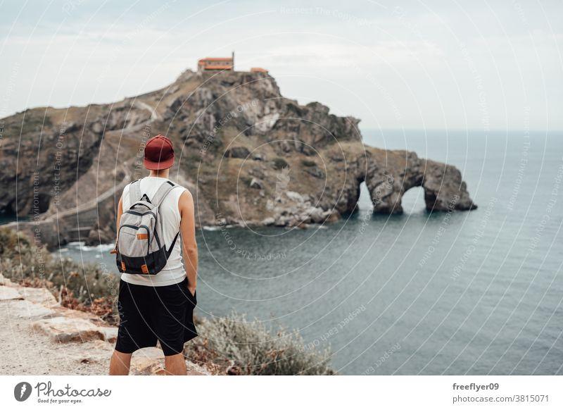 Junger Mann mit Hut vor der Insel Gaztelugatxe eine Tourist Backpacker Rucksack Tourismus Besuch Sightseeing romantisch Vizcaya Spanien Bermeo X Jahrhundert