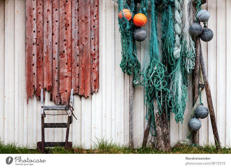 Maritimes Stillleben an einer Hauswand in Norwegen netze fischernetz boje holz brett karre sackkarre leine seil tau tauwerk maritim hafen holzhaus zierrat