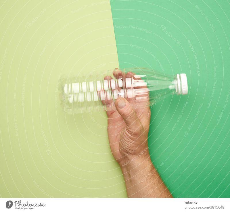 männliche Hand hält leere transparente Plastikflasche auf grünem Hintergrund Flasche Kunststoff liquide Konzept Atelier durchsichtig Sauberkeit Wasser Container