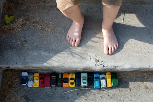 Spielzeugautos in einer Reihe auf Betontreppen in der Nähe von Kinderfüßen; Spiel im Freien Spielen spielerisch Fuß Zehen Linie aufgereiht freies Spiel offen