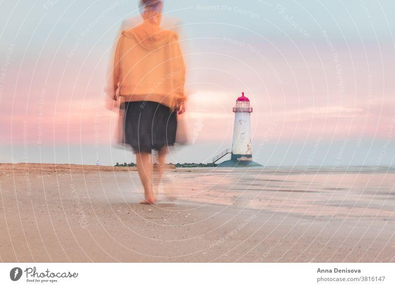 Verschwommene Bewegung der sich auf den Leuchtturm zu bewegenden Frau verschwommen Ayr-Spitze talacre Ufer Wales MEER laufen Person reisen Unschärfe Dame Strand