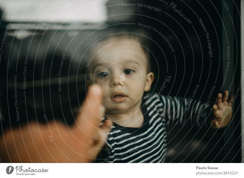Kind spielt mit Vater durch Fenster durch Glas durch das Fenster authentisch Kleinkind Kindheit Reflexion & Spiegelung Quarantäne heimwärts Isolation