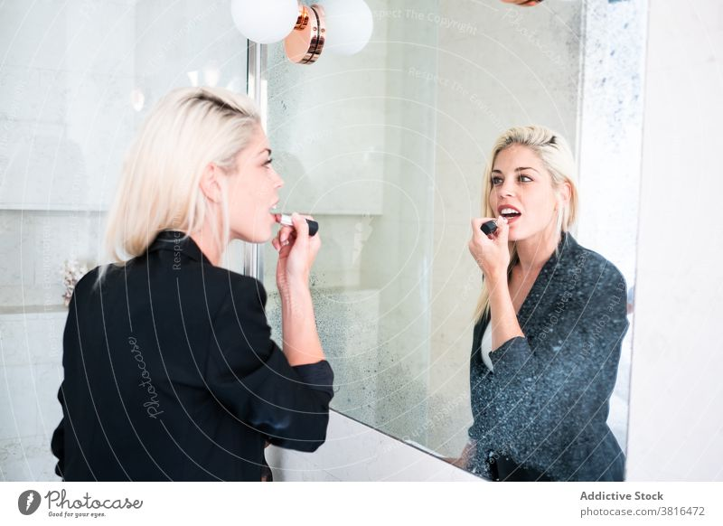 Blonde Frau Anwendung Lippenstift in der Nähe von Spiegel Make-up bewerben Morgen Routine Reflexion & Spiegelung Kosmetik Schönheit jung Farbe Bad Hautpflege