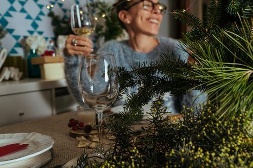 Familiengespräche beim Weihnachtsessen, zwei Schwestern sitzen am geschmückten Tisch mit Gläsern Weißwein in der Hand. Weihnachten Erntedankfest Abendessen