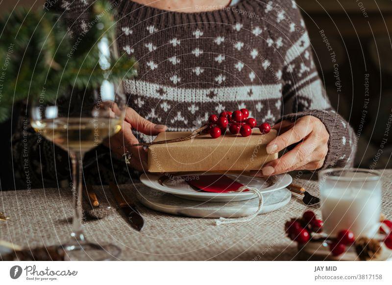 Frau öffnet Weihnachtsgeschenk, während sie am gedeckten Tisch sitzt, Family Together-Konzept Weihnachten offen Geschenk Weihnachtstisch decken Glück Menschen
