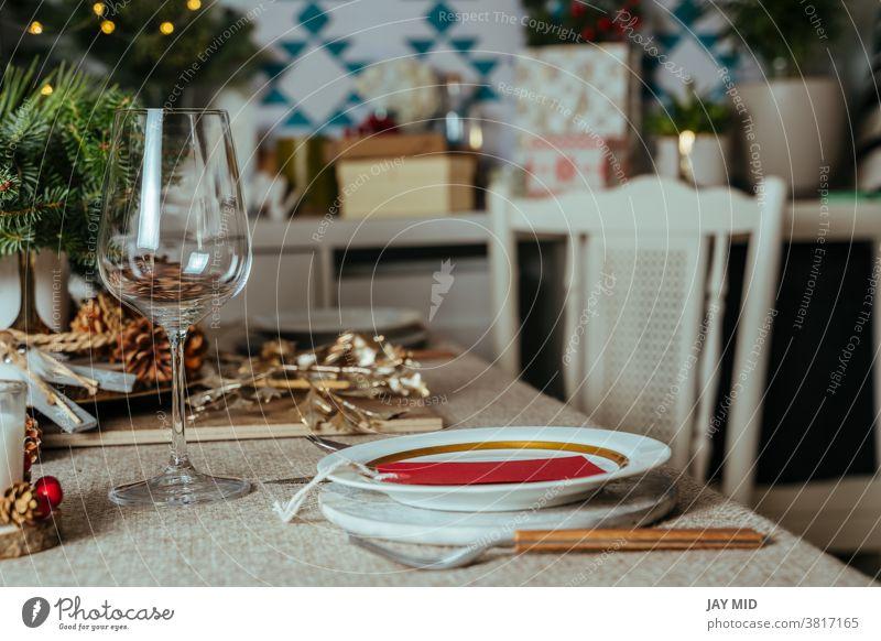Gemütliche weihnachtliche Tischdekoration, mit Kiefernzweigen rustikale Tischdecke im Wohnzimmer des Hauses. Europäischer Stil mit Weihnachtsbeleuchtung.