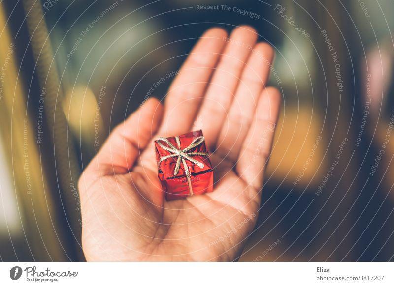 Hand hält ein kleines rotes Geschenk zum Geburtstag oder Weihnachten. verpackt Überraschung Schleife Weihnachtsgeschenk geben schenken Gabe