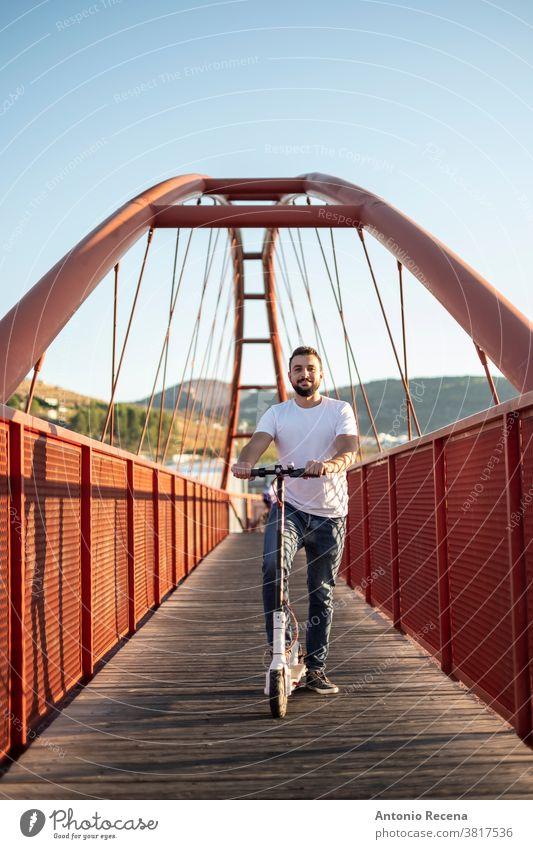 Mann fährt Elektroroller auf roter Fußgängerbrücke Tretroller Schlittschuh Transport elektrisch Fahrzeug urban Männer arabisch attraktiv Person Menschen