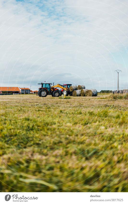 Roter Traktor, der während der Erntezeit einen Anhänger mit Strohballen belädt Erntekampagne Paket Grasland Landschaft Fahrzeug Maschine vertikal Haufen