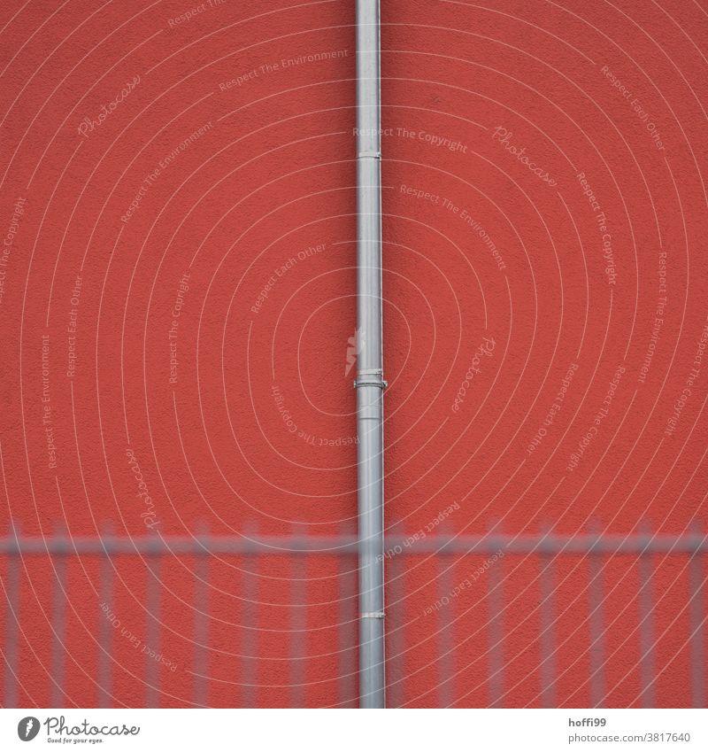 Fallrohr mit verschwommenem  Zaun an einer roten Wand Regenrinne Abluftrohre rote fassade rote wand Geometrie geometrisch minimalistisch Minimalismus