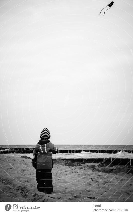 Ein Kind lässt am Strand am Meer den Drachen steigen Kleinkind Himmel Drachen steigen lassen fliegen Wind Freude Kindheit Herbst Lenkdrachen Luft Wolken Buhnen