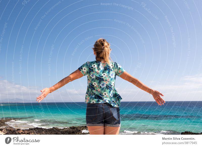 Blonde Frau auf Fuerteventura auf den Kanarischen Inseln. Architektur Strand blond blau Boot Gebäude Kanaren Kanarienvogel Kanarische Inseln Küste Küstenlinie