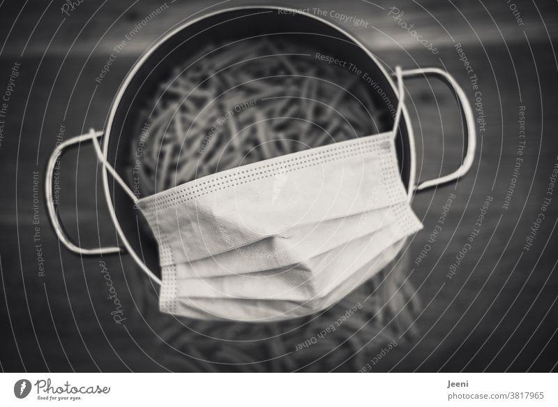 Nudeln in einem Kochtopf mit einer Mund-Nasen-Schutzmaske. Hamsterkäufe der Deutschen in der Corona Pandemie (2020) für die Quarantäne I corona thoughts Virus