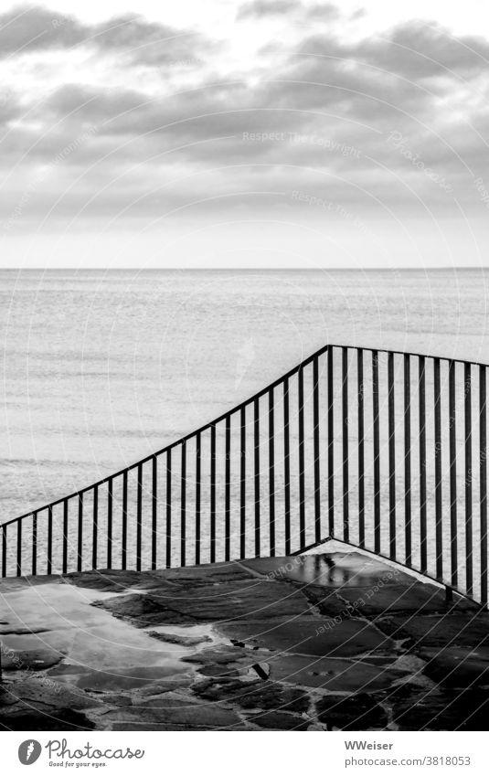 Die nasse Treppe führt herunter zum Strand Meer Geländer Stufen Stein Wasser Wolken Himmel Regen feucht Menschenleer Küste Ostsee grau trüb melancholisch See