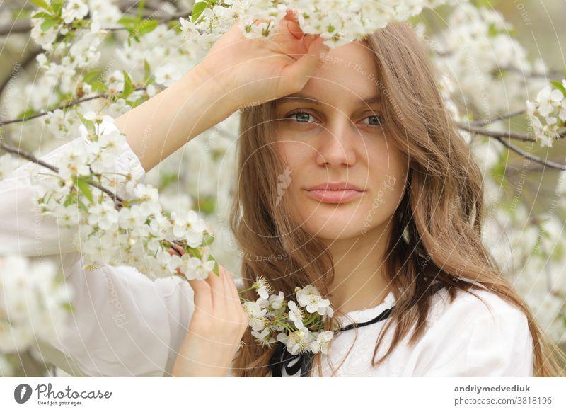 Porträt eines glücklichen Mädchens in Frühlingsblumen. Ein schönes junges Mädchen mit Blumenstrauss in der Nähe einer Blumenwand. Behaarung Wand geblümt Sommer