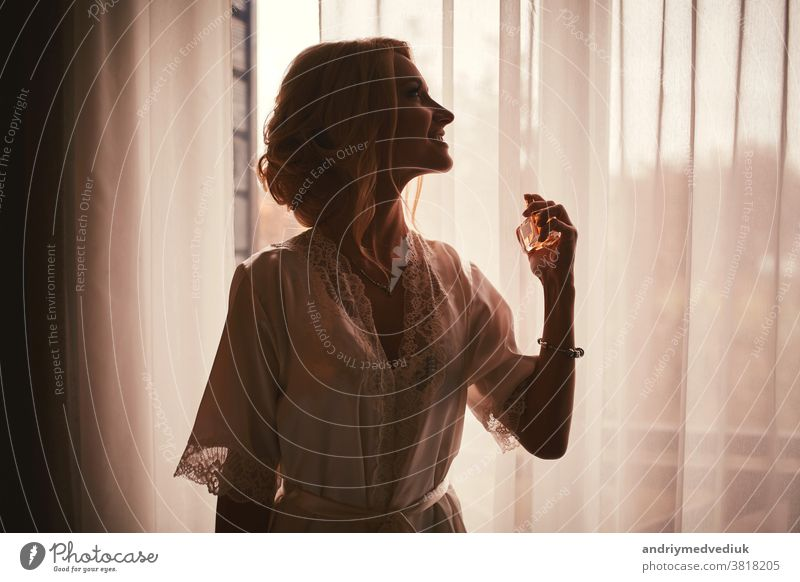 Ein Mädchen in einem weißen Satinmantel mit Ausschnitt und Manikürfranzösisch hält einen Flakon mit Parfüm und Spritzern am Handgelenk. Morgen der Braut im Haus am Fenster