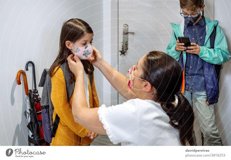 Mutter setzt ihrer Tochter die Maske auf vorbereitend Gesichtsmaske zur Schule gehen covid-19 Coronavirus Schutzmaske korrekt passende Maske