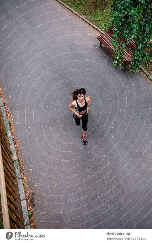 Luftaufnahme der Läuferin Frau rennen Asphalt Stadtpark genießend Overhead durchhalten heiter Sport Draufsicht Athlet schlanke Fitness Gesundheit Übung jung