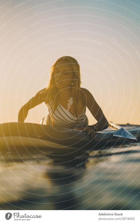 Gelassene Frau auf Surfbrett im Meer Lügen MEER sich[Akk] entspannen Sonnenuntergang schlank Badeanzug Wasser winken Himmel Erholung Sommer Badebekleidung ruhen