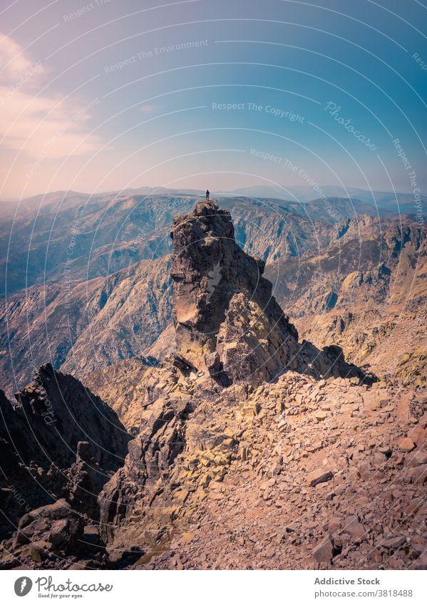 Unbekannter Tourist auf rauem Felsen unter bewölktem Himmel Reisender bewundern Kamm Hochland Natur Fernweh erkunden Blauer Himmel wolkig atemberaubend
