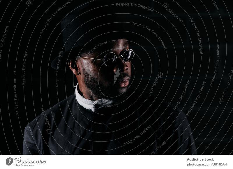 Ruhiger stilvoller Mann in dunklem Studio Stil schwarz Stoff Atelier Ring Hut Bekleidung trendy Sonnenbrille männlich ethnisch Afroamerikaner rund Form ernst