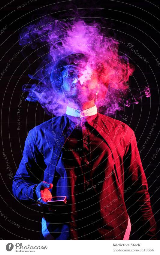 Schwarzer Mann rauchend im Studio mit Neon-Beleuchtung neonfarbig Licht Rauch Raps Dampf Verdunstung Stil Outfit selbstbewusst männlich ethnisch schwarz