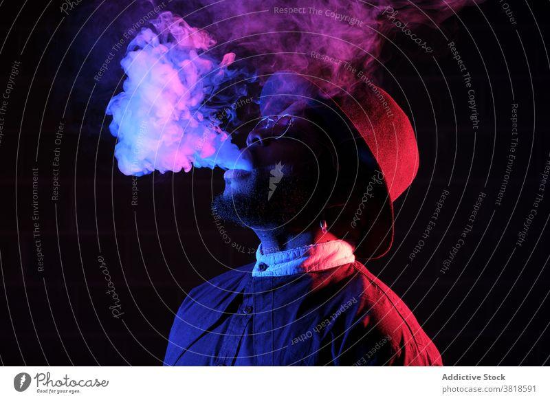 Ethnischer Mann raucht im Studio mit Neonlicht Rauch Raps Verdunstung Stil neonfarbig Licht leuchten dunkel Atelier männlich ethnisch schwarz Afroamerikaner