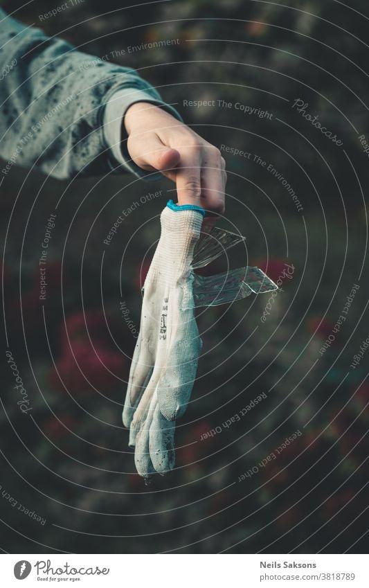 Hand, die einen Handschuh mit eingeklebten Eisplatten hält Garten Gartenarbeit gefroren kalt Wasser Frost menschlich menschliche Hand Finger Gartenhandschuh
