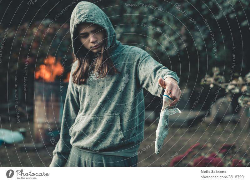 Junge mit langen Haaren in grünem Kapuzenpulli, der einen Handschuh mit aufgeklebten Eisplatten hält Garten Gartenarbeit gefroren kalt Wasser Frost menschlich